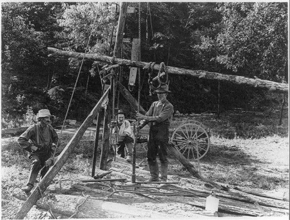 Vintage photo of men drilling a well by hand